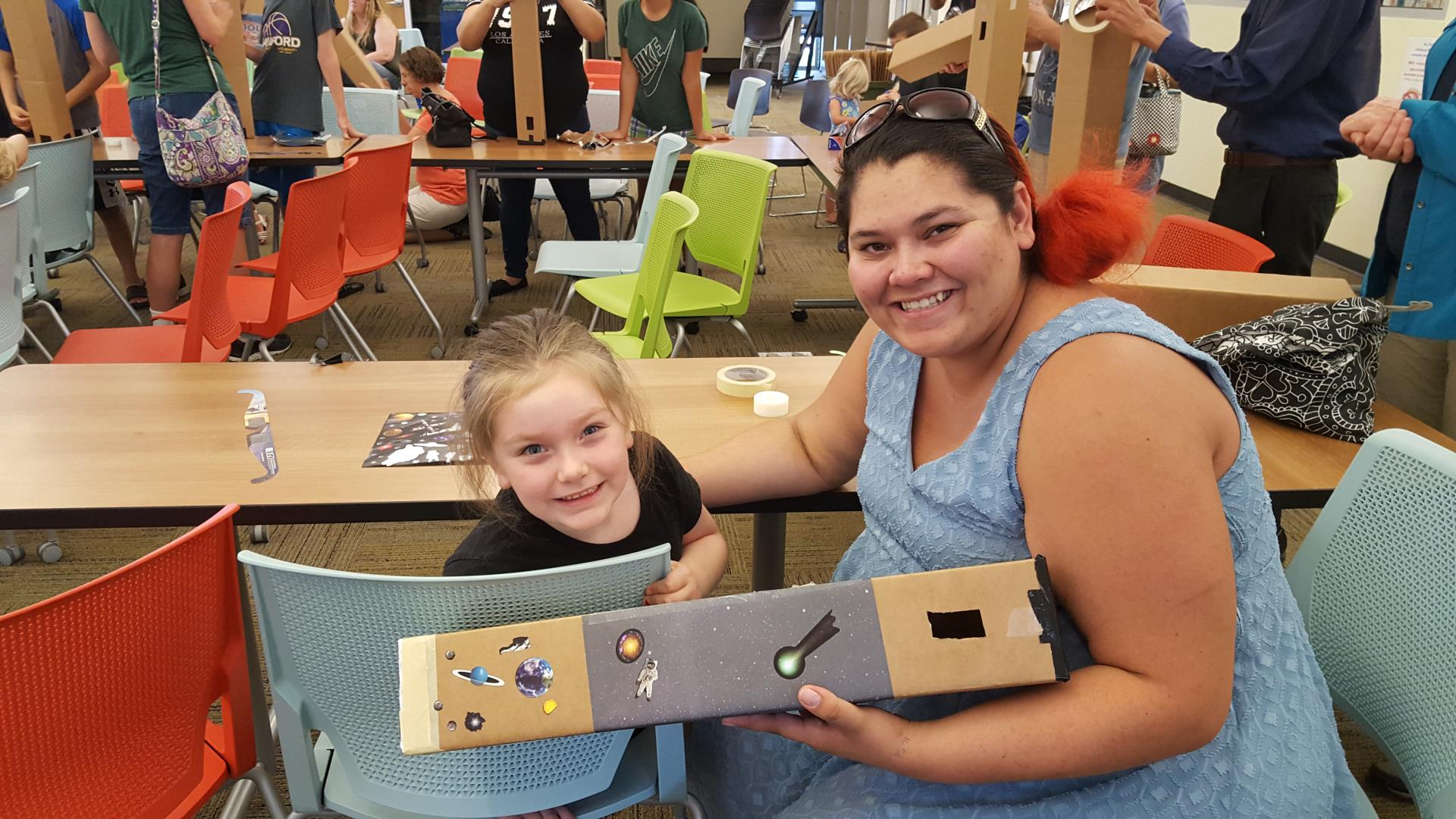 Mother and daughter displaying their completed and decorated pinhole eclipse viewer