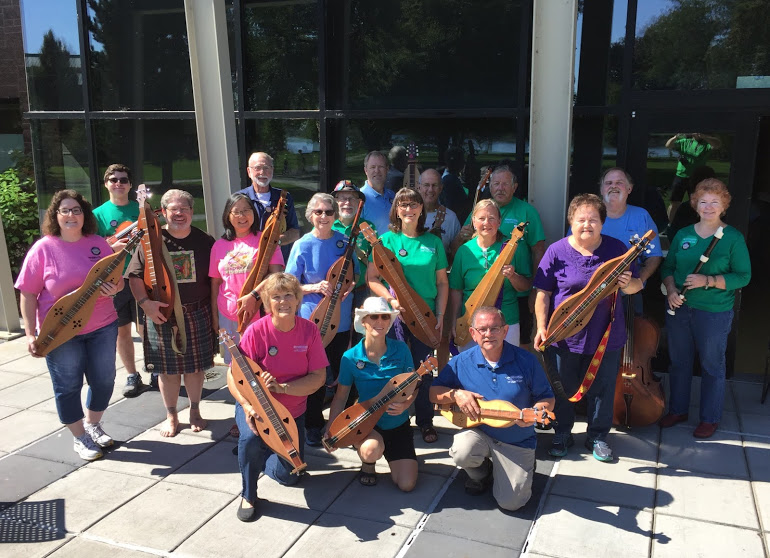 Members of the 3 Rivers Dulcimer Society posing with assorted instruments including dulcimers, guitars, cellos, and recorders.