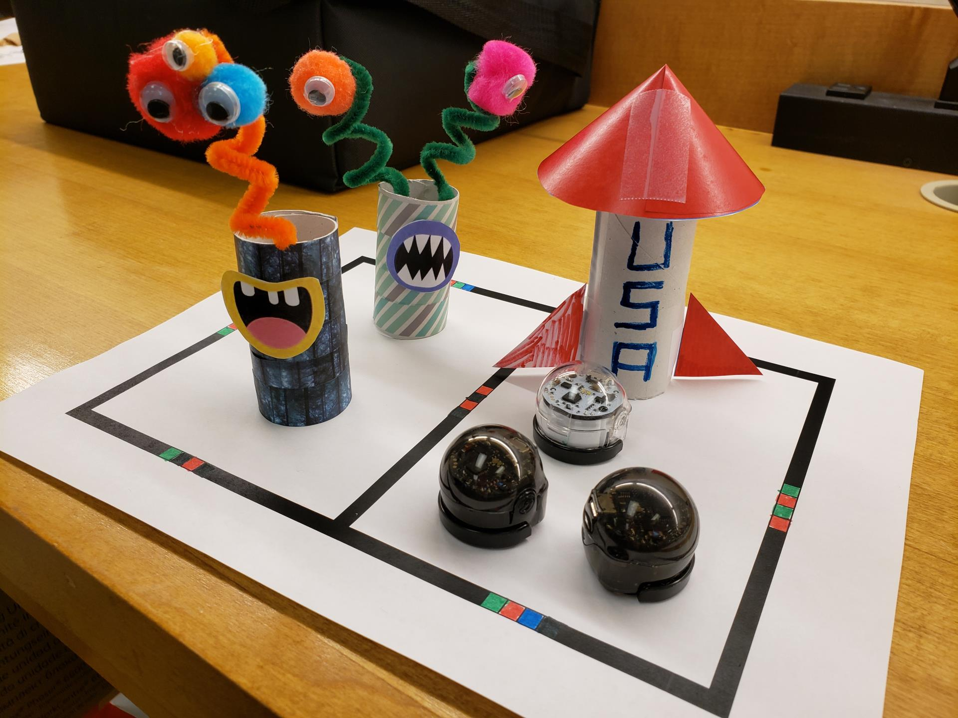Ozobot robots with space costumes in the shape of rockets and aliens