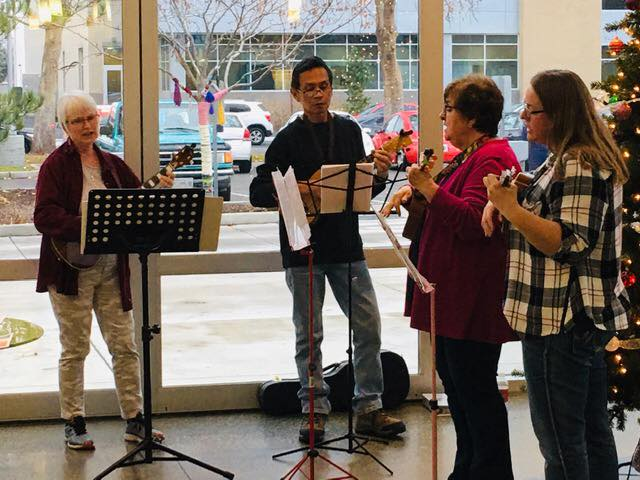 Members of the library's ukulele club leading a holiday singalong in the lobby.